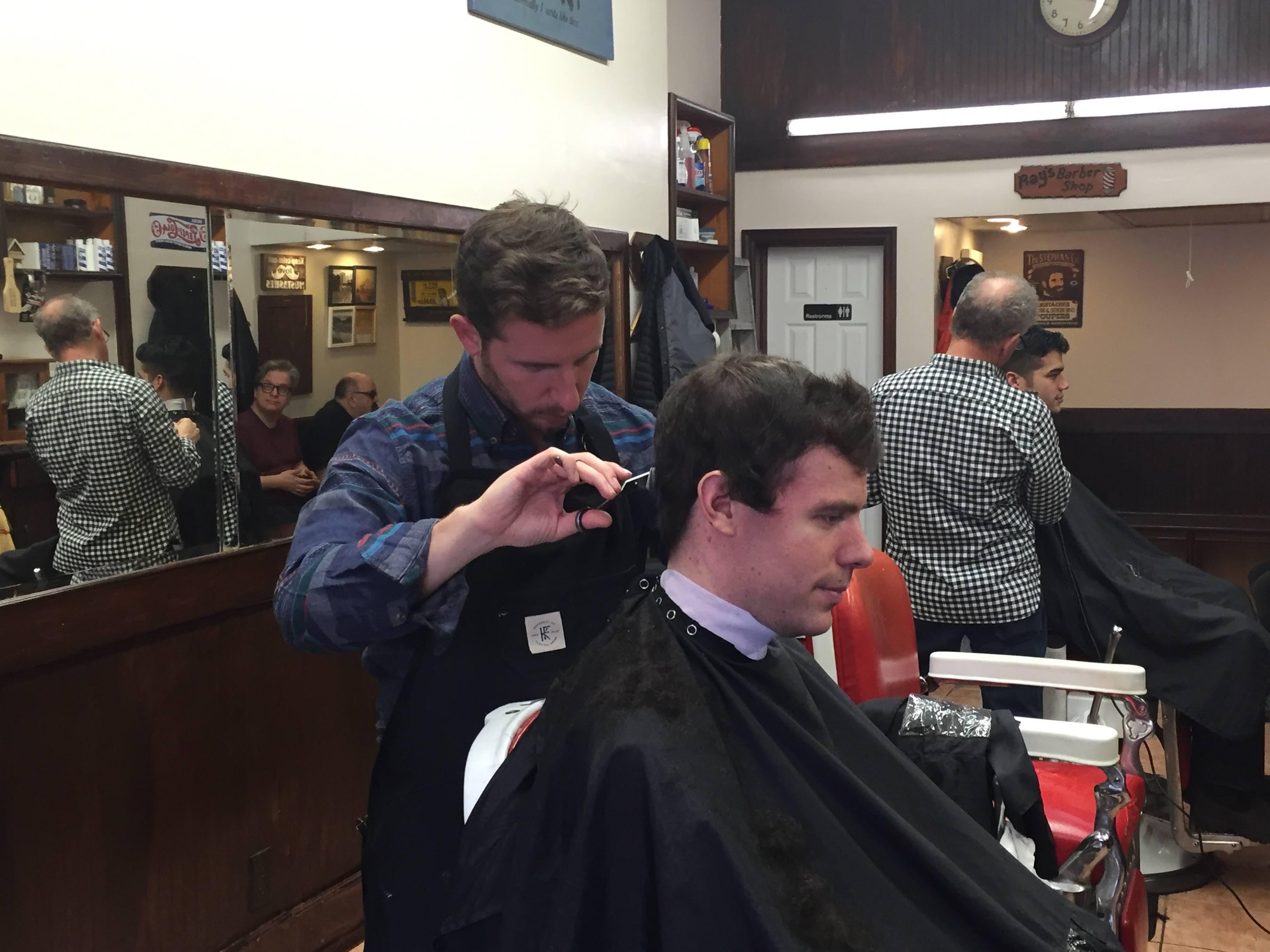 Ray Jr. cutting hair at Ray's Barber Shop in Inwood NY